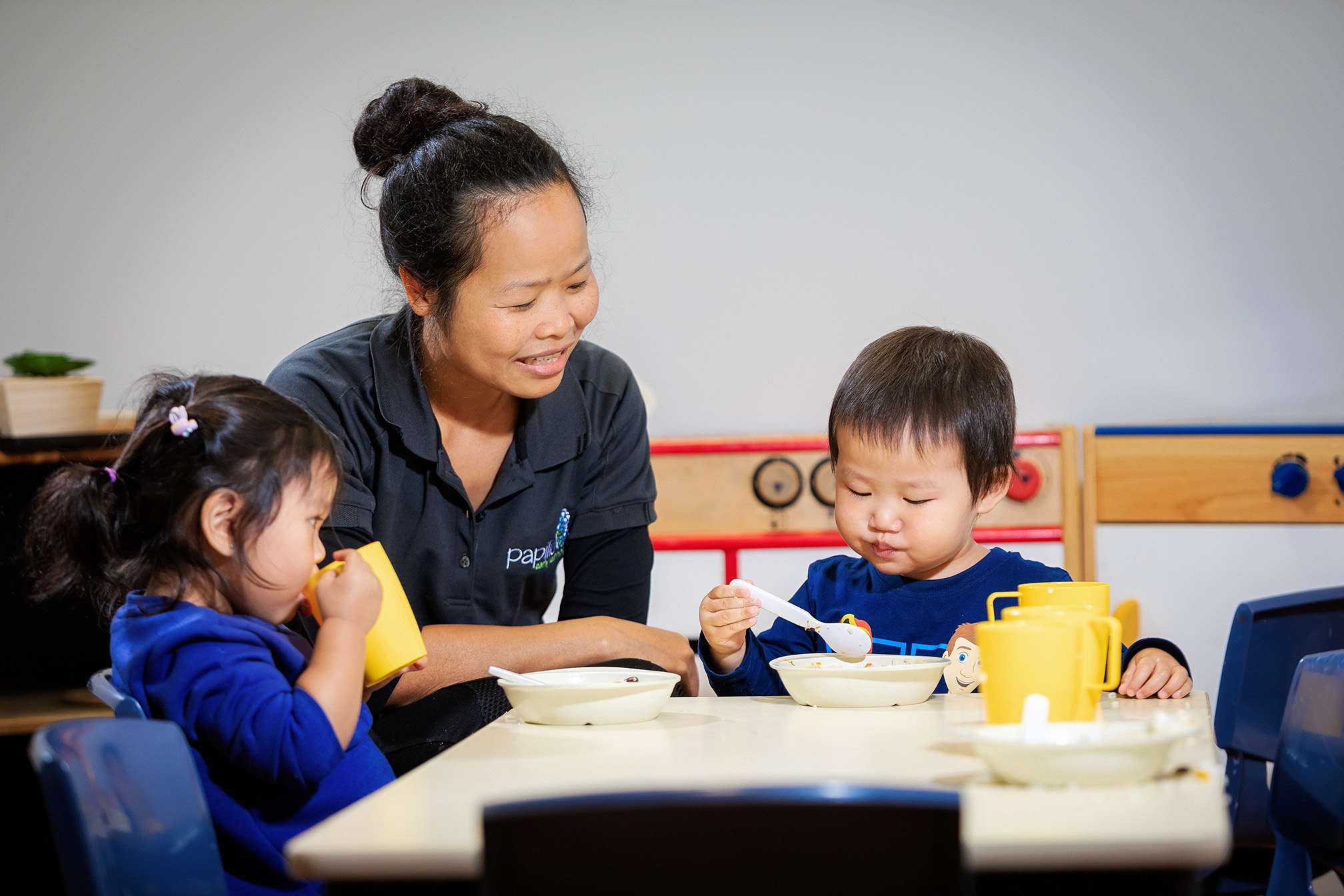 Child care educator sitting at table with young children eating lunch